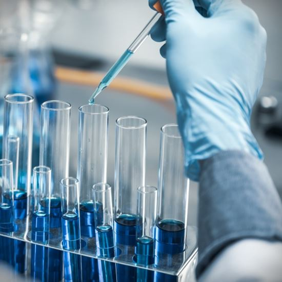 Gloved hand holding pipette with test tubes of blue fluid