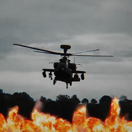 Dramatic image of Apache above explosions