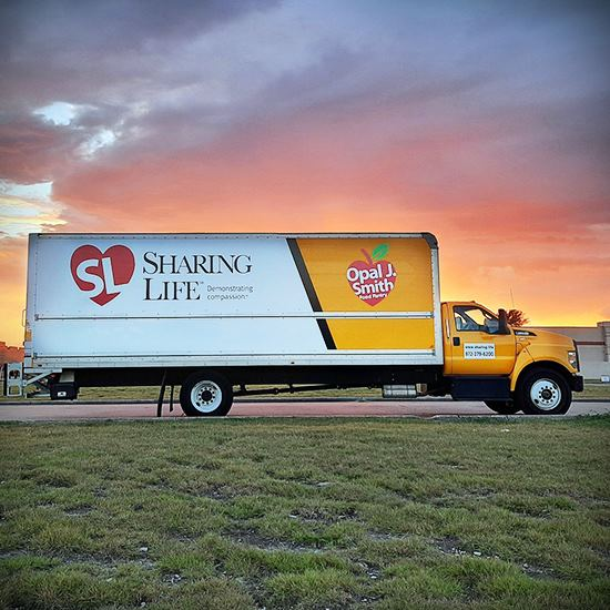 Big white truck that says Sharing Life under a sunset