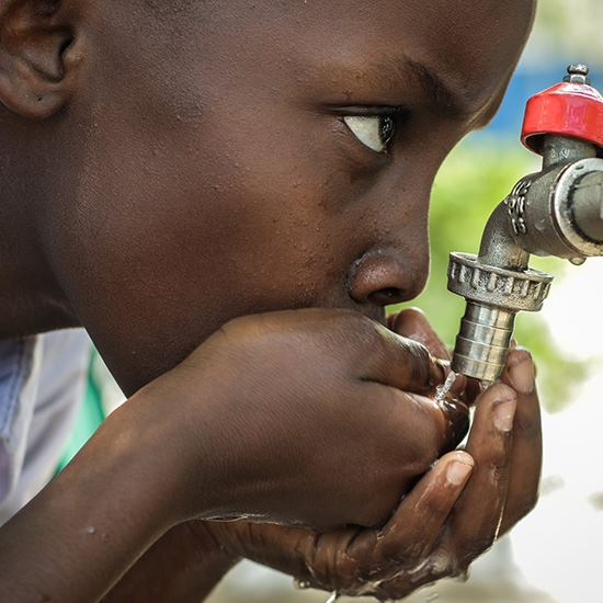 Boy drinking water from a faucet