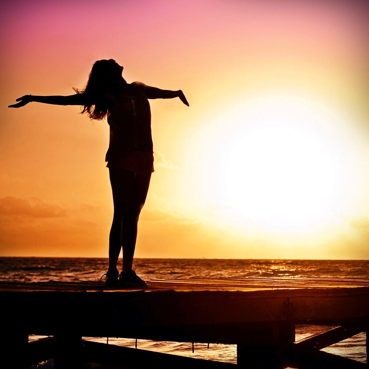 Woman silhouetted in the setting sun
