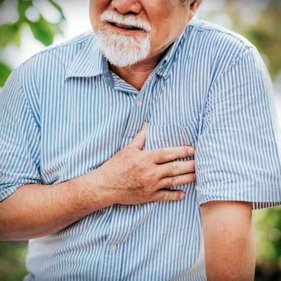 Middle-aged man with a gray beard clutching his chest in pain