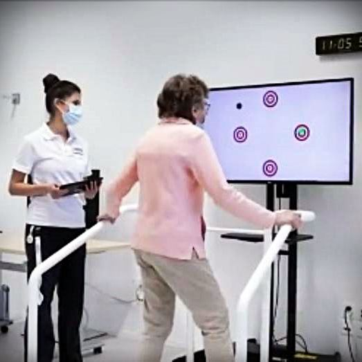 Senior woman on a treadmill with video and researcher
