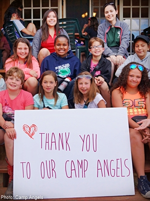 a bunch of kids at camp on a porch with a sweet handmande thank you sign